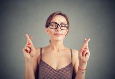 La femme mignonne en verres croise des doigts, faisant un souhait images libres de droits