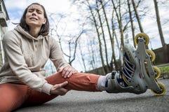 La femme mignonne est tombée équitation sur des patins de rouleau image libre de droits