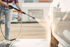 La femme mignonne nettoie des roues de voiture avec l'arme ? feu d'eau photographie stock libre de droits