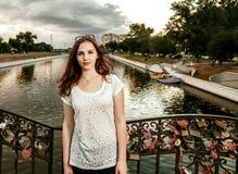 La femme mignonne sur le pont avec amour ferme à clef sur la barrière regardant l'appareil-photo Photographie stock