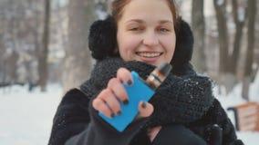 La femme mignonne tient la cigarette électronique en parc d'hiver clips vidéos
