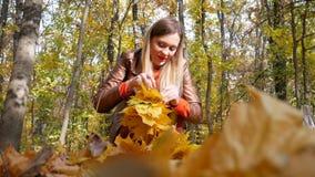 La femme mignonne tricote la guirlande jaune de feuille banque de vidéos
