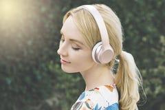 La femme millénaire caucasienne est inspirée par la musique qu'elle entend dans des ses écouteurs photographie stock libre de droits