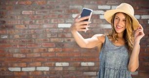 La femme millénaire en été vêtx prendre le selfie contre le mur de briques rouge image libre de droits