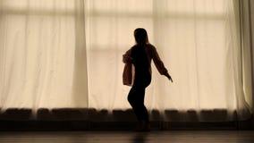 La femme mince danse dans une salle de préparation contre les fenêtres énormes avec des rideaux, silhouette de figure banque de vidéos