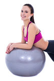 La femme mince heureuse dans les sports portent avec la boule de forme physique d'isolement sur le wh Image libre de droits