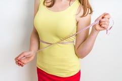 La femme mince mesure sa taille avec une bande de mesure Photo libre de droits