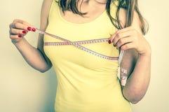 La femme mince mesure son sein avec une bande de mesure Photographie stock