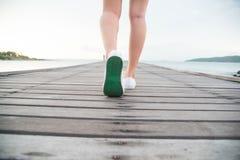 La femme a mis dessus les chaussures de toile blanches Photographie stock