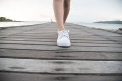 La femme a mis dessus les chaussures de toile blanches Photo stock