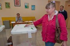 La femme a mis le vote d'élection avec des candidats pour le maire de Mosco Photographie stock