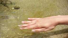 La femme a mis la main en eau froide le jour ensoleillé dans le mouvement lent Surface claire émouvante de l'eau de main femelle banque de vidéos