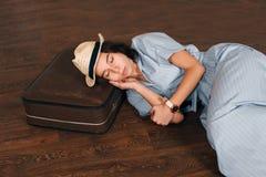 La femme a mis sa tête sur la valise et les sommeils image stock