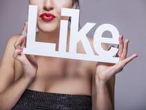 La femme modèle avec les lèvres rouges avec les lettres blanches AIMENT Photo libre de droits