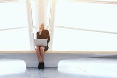 La femme moderne appelle par l'intermédiaire du téléphone de cellules, tandis que se repose avec le filet-livre dans le bureau Images libres de droits