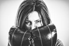 La femme moderne courageuse et furieuse d'affaires avec des gants de boxe est image libre de droits