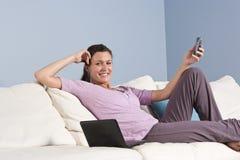 La femme moderne a détendu sur le divan avec le téléphone, ordinateur portatif Photos stock