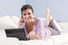 La femme moderne a détendu sur le divan avec le téléphone, ordinateur portatif photographie stock libre de droits