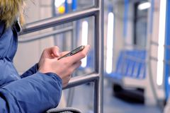La femme monte dans une voiture de souterrain vide et observe une vidéo sur son smartphone Vue de côté, plan rapproché de mains photo stock