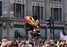 La femme monte le feu de signalisation au cirque d'Oxford, Londres, pour obtenir une meilleure vue de Pride Parade gai photos stock