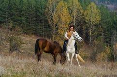 La femme monte sur un cheval blanc images libres de droits