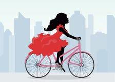 La femme monte une bicyclette sur le fond de la ville Photographie stock libre de droits