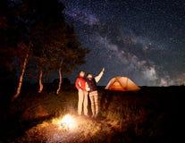 La femme montre l'homme au ciel étoilé de soirée avec la manière laiteuse Images libres de droits