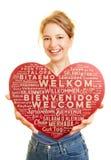 La femme montre le coeur avec la salutation bienvenue dans beaucoup de langues Image libre de droits