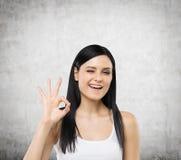 La femme montre le signe correct Fond concret Photo stock