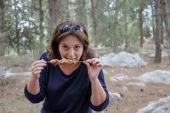 La femme mord un chiche-kebab grillé Image stock