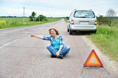 La femme émotive s'asseyant sur la route près du signe de secours manie maladroitement  Image stock