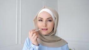 La femme musulmane applique la poudre compacte regardant le miroir banque de vidéos