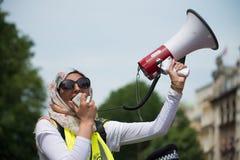 La femme musulmane avec le mégaphone à la compteur-démo par le groupe de pression unissent contre le fascisme dans Whitehall, Lon Images stock