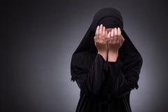 La femme musulmane dans la robe noire sur le fond foncé photographie stock libre de droits