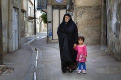La femme musulmane dans le tchador se tient dans la cour avec la petite fille Image libre de droits