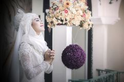 La femme musulmane dans la robe blanche a fermé ses yeux se tenant et priant Photos stock