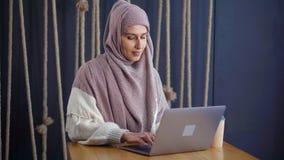 La femme musulmane introduit des messages sur l'ordinateur portable en café, seul se reposant clips vidéos
