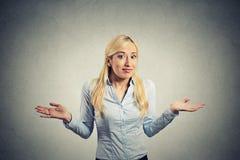 La femme naïve confuse arme gesticule des épaules image libre de droits