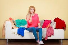 La femme ne sait pas quoi porter se reposer sur le divan Image stock