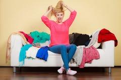 La femme ne sait pas quoi porter se reposer sur le divan Images stock