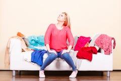 La femme ne sait pas quoi porter se reposer sur le divan Photographie stock libre de droits