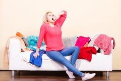 La femme ne sait pas quoi porter se reposer sur le divan Photos stock