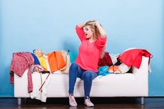 La femme ne sait pas quoi porter se reposer sur le divan Image libre de droits