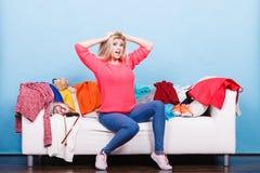 La femme ne sait pas quoi porter se reposer sur le divan Photos libres de droits