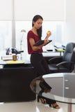 La femme nerveuse d'affaires avec l'anti boule d'effort tient le comprimé Image stock