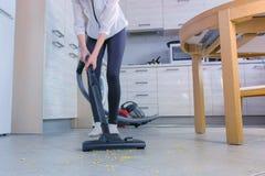 La femme nettoie à l'aspirateur le plancher de cuisine Elle range les flocons d'avoine dispersés sur la tuile grise photos stock