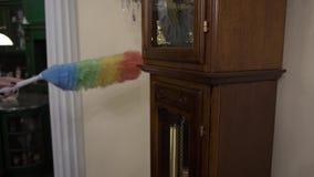 La femme nettoie la grande horloge de la poussière avec une brosse Concept à la maison de nettoyage banque de vidéos