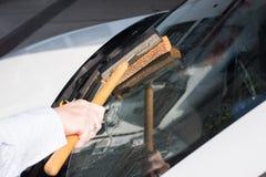La femme nettoie le pare-brise de sa voiture photos libres de droits