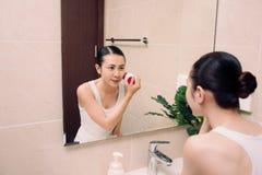 La femme nettoie son visage avec une brosse pour le nettoyage profond image libre de droits