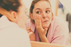 La femme nettoyant son visage avec frottent dans la salle de bains photos libres de droits